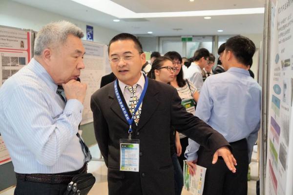 本所參與壁報比賽研究生李榮祐(右一)向壁報評審進行說明情景